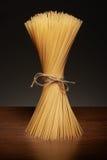Pâtes sèches de spaghetti sur la table en bois foncée sur le gris Photos libres de droits