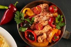 Pâtes savoureuses avec du fromage, le poulet frit et le verre de vin sec rouge Photographie stock