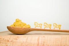 Pâtes sous forme d'animaux et de cuillère sur un fond blanc photo libre de droits