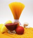 Pâtes, spaghetti, papier, ail, tomate et sauce tomate Image libre de droits