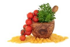 Pâtes, tomates et herbe de basilic Photographie stock libre de droits