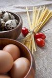 Pâtes, tomates et oeufs secs dans des cuvettes en bois sur SA Photo stock
