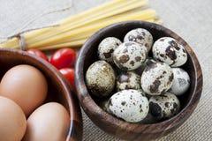 Pâtes, tomates et oeufs secs dans des cuvettes en bois sur SA Image libre de droits