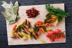 Pâtes, tomates et poivre sur la table Photo stock