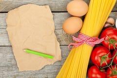 Pâtes, tomates, oeufs et papier brun vide Photographie stock
