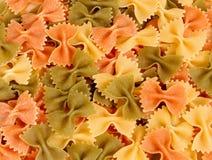 Pâtes tri-colorées sèches de farfalle Photographie stock