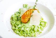 Pâtes vertes avec les poissons grillés Photo stock