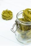 Pâtes vertes crues de tagliatelles sur un pot en verre images stock