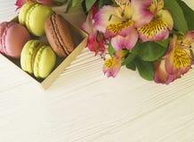 Pâtisserie de couleur de Macaron dans une boîte sur la fleur en bois blanche d'alstroemeria de fond de boulangerie Image stock