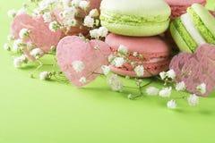 Pâtisserie de macaronis sur un fond de couleur en bon état avec des coeurs le jour de l'amour Images libres de droits