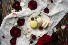 Pâtisserie de trois macarons se trouvant d'un plat entouré par les bloss roses photo libre de droits
