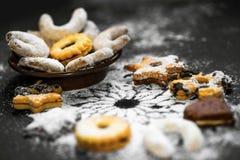 Pâtisserie douce décorative de Noël arrosée avec du sucre sur le noir Photographie stock libre de droits
