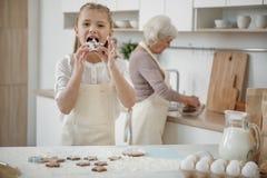 Pâtisserie douce savoureuse d'enfant gai dans la cuisine Photos libres de droits