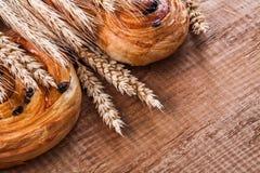 Pâtisserie savoureuse de raisin sec d'oreilles d'or de blé sur en bois de chêne Photo stock