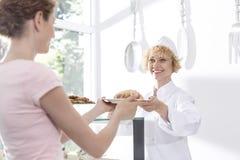 Pâtisserie servante de sourire de chef mûr au jeune client au compteur dans le restaurant images libres de droits
