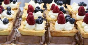 Pâtisseries avec la framboise et les myrtilles et la crème anglaise à vendre photo stock