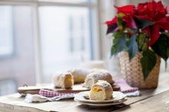 Pâtisseries de Noël sur une table près d'une fenêtre et d'une fleur avec les feuilles rouges photos libres de droits