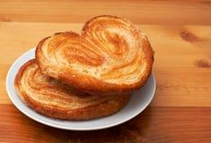 Pâtisseries plus palmier sur la soucoupe Photographie stock libre de droits
