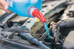 Påfyllning av vattenbehållaren med frostskyddsvätska i motorrummet av en bil royaltyfri bild