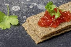 Pães estaladiços com caviar e salsa no fundo preto fotos de stock