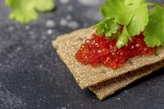 Pães estaladiços com caviar e salsa no fundo preto fotos de stock royalty free