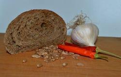 Pão, alho e pimentas para uma refeição Imagem de Stock