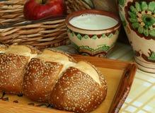 Pão branco com sementes e leite em um potenciômetro de argila Foto de Stock