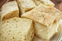 Pão branco macio fresco com crosta em uma placa em uma tabela de madeira Fotos de Stock