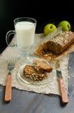 Pão caseiro com as maçãs no papel de envolvimento e no vidro do leite na placa Imagens de Stock Royalty Free