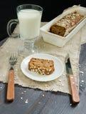 Pão caseiro com as maçãs no papel de envolvimento e no vidro do leite na placa branca Fotografia de Stock