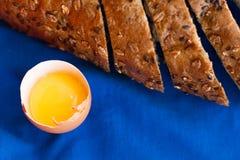 Pão caseiro com cereais e o ovo fresco em um fundo azul Foto de Stock
