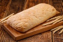 Pão caseiro saboroso fresco em uma placa de madeira Ainda uma vida monótono com pão e spikelets do centeio Imagem de Stock