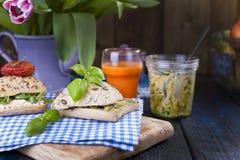 Pão com abacate, tomates e queijo em uma toalha azul e em uma placa Sanduíches para o café da manhã e o suco Uma dieta saudável p Imagens de Stock