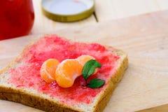 Pão com doce de morango e parte alaranjada foto de stock