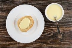 Pão com leite condensado do doce na placa, bacia com leite fotografia de stock royalty free