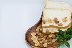 Pão com o cereal e as amêndoas decorados com a folha verde no woode Fotos de Stock