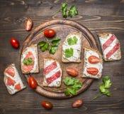 Pão com os tomates do queijo com ervas em uma placa de corte na opinião superior do fundo rústico de madeira Imagens de Stock