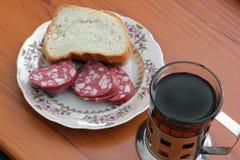 Pão com salsicha em uma placa Chá preto do café da manhã imagem de stock