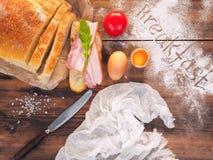 Pão cortado com uma fatia de presunto, de gema no shell e de tomate Ainda vida com o café da manhã da palavra, na tabela de madei Imagem de Stock Royalty Free