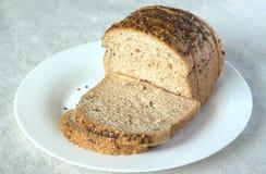 Pão cortado da grão na placa branca no pano de tabela cinzento Foto de Stock Royalty Free