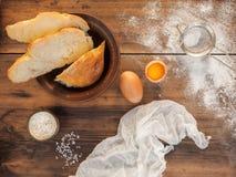 Pão cortado, dispersado a farinha, o sal, a gema e o tecido Ainda vida no fundo da tabela de madeira velha, parte superior Foto de Stock