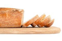 Pão cortado em uma placa de desbastamento de madeira fotografia de stock royalty free