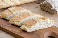 Pão cortado em uma placa de madeira Imagens de Stock