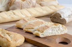 Pão cortado em uma placa de madeira Fotografia de Stock Royalty Free