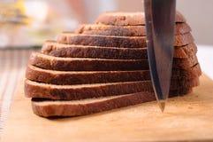 Pão cortado em uma placa e em uma faca de madeira de estaca Fotografia de Stock