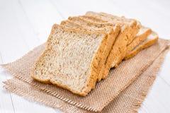 Pão cortado na tabela de madeira branca Foto de Stock Royalty Free