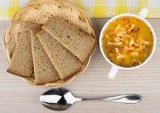 Pão da sopa de ervilha na cesta e colher na tabela Imagem de Stock