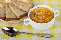 Pão da sopa de ervilha na cesta e colher no guardanapo Fotos de Stock