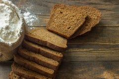 Pão de centeio cortado em uma tabela de madeira com o saco da farinha branca imagem de stock royalty free