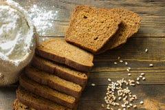 Pão de centeio cortado em uma tabela de madeira com o saco da farinha branca Imagens de Stock Royalty Free